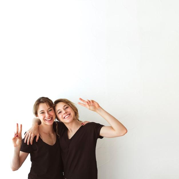 Deux soeurs faisant signe de victoire sur fond blanc Photo gratuit
