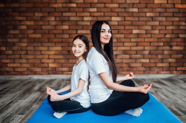 Deux sœurs en forme, adossées l'une à l'autre au gymnase et pratiquant le yoga. Photo Premium