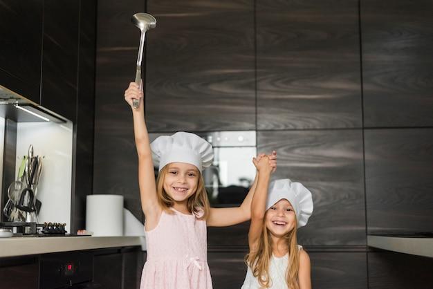 Deux soeurs heureuse portant la toque dans la cuisine en tenant leurs mains Photo gratuit