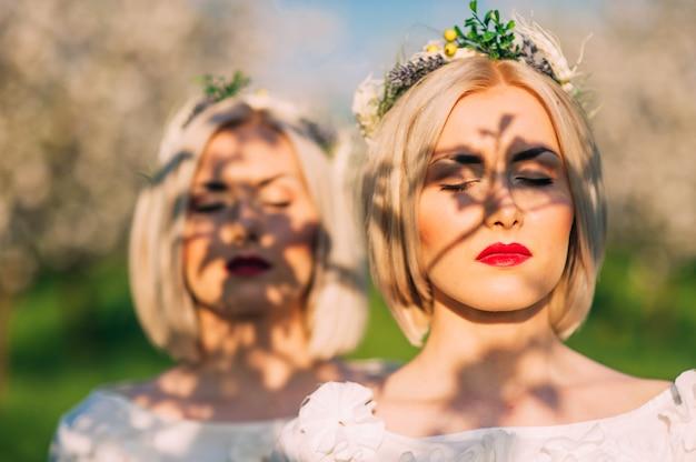Deux soeurs jumelles dans un verger de cerisiers Photo Premium