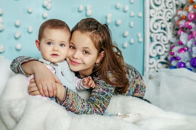 Deux sœurs s'embrassent. enfants. le concept de joyeux noël Photo Premium