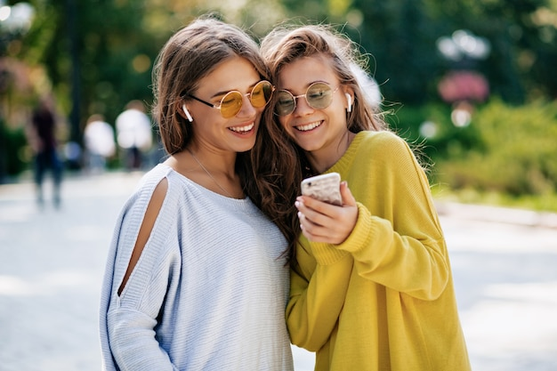 Deux Sœurs Souriantes Drôles Faisant Selfie Sur Smaptphone Et écoutant De La Musique, Posant Dans La Rue, Humeur De Vacances, Sentiment Positif Fou, Lunettes De Soleil De Vêtements Lumineux D'été. Photo gratuit