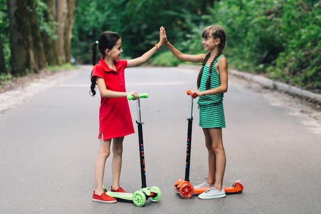 Deux, sourire, filles, debout, sur, scooter, donnant, haute, cinq, geste, sur, route Photo gratuit