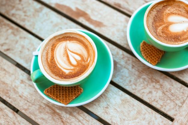 Deux tasse de café avec art au lait en forme de coeur et gaufres Photo gratuit