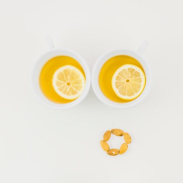 Deux tasse de thé au gingembre avec une tranche de citron et amandes isolées sur fond blanc Photo gratuit