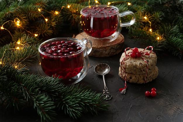 Deux tasses avec boisson épicée de noël aux canneberges et gâteaux Photo Premium