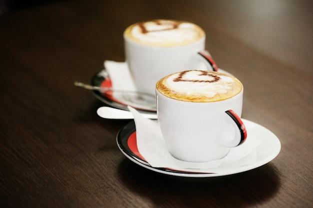 Deux tasses de café avec motif coeur dans une tasse blanche sur une table en bois Photo Premium