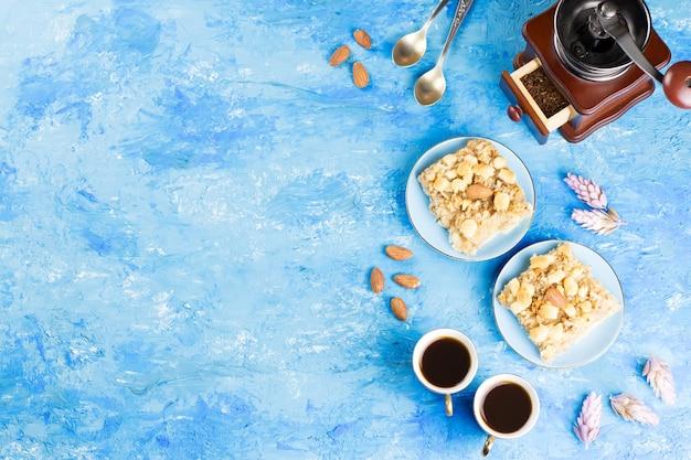 Deux Tasses à Café, Moulin à Café Et Tarte Aux Pommes Sur Bleu Artistique. Vue De Dessus Photo Premium