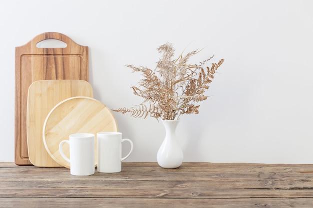 Deux Tasses Et Fleurs Séchées Sur Cuisine Blanche Photo Premium
