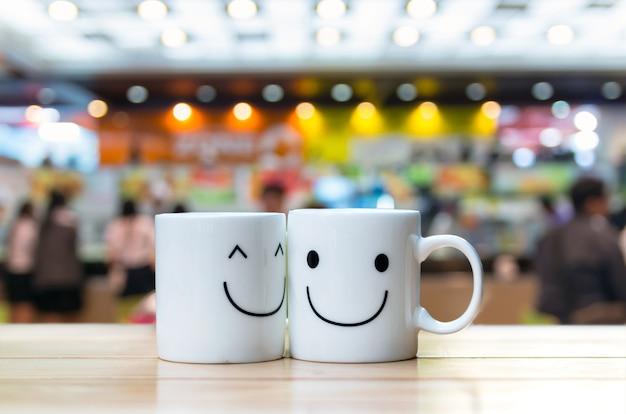 Deux tasses heureux sur fond de magasin de café flou Photo Premium