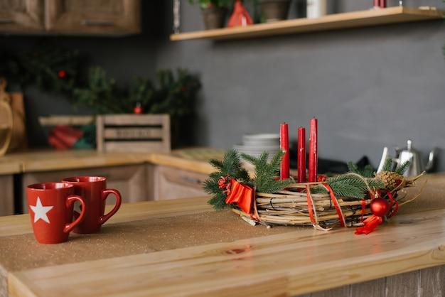 Deux Tasses Rouges Et Une Guirlande De Noël Avec Des Bougies Sur La Table, Décor De Maison De Vacances Photo Premium