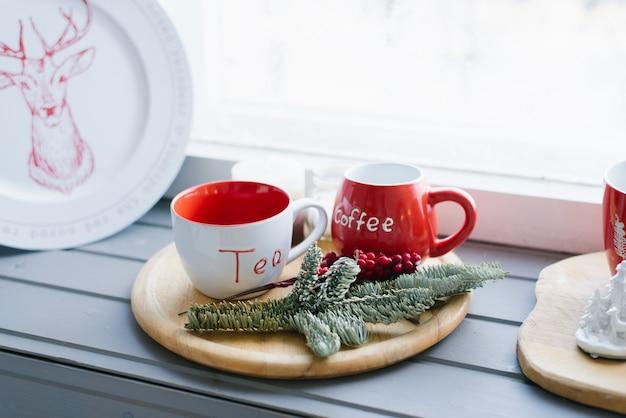 Deux Tasses Rouges Sur Un Plateau En Bois Sur Le Rebord De La Fenêtre, Décor De Noël Photo Premium