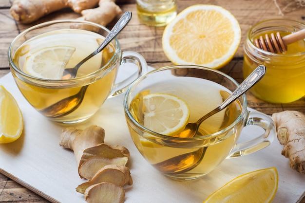 Deux tasses de tisane naturelle au gingembre, citron et miel sur une surface en bois. Photo Premium