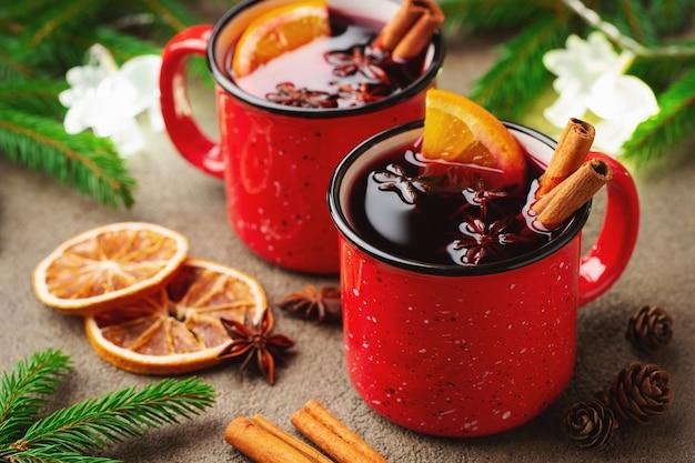 Deux tasses de vin chaud de noël ou gluhwein avec des épices et des tranches d'orange sur une table rustique Photo Premium