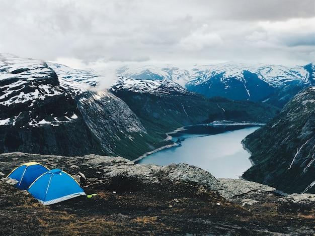 Deux tentes bleues se dressent devant une magnifique vue sur la montagne Photo gratuit