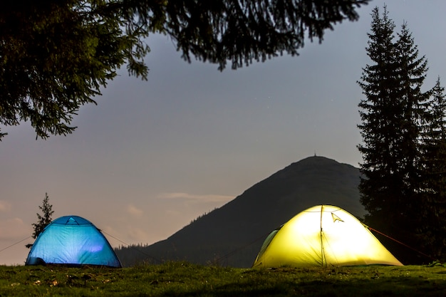 Deux tentes de touristes éclairées sur la forêt herbeuse verte éclaircie sur la montagne sombre et clair espace copie ciel étoilé bleu. Photo Premium