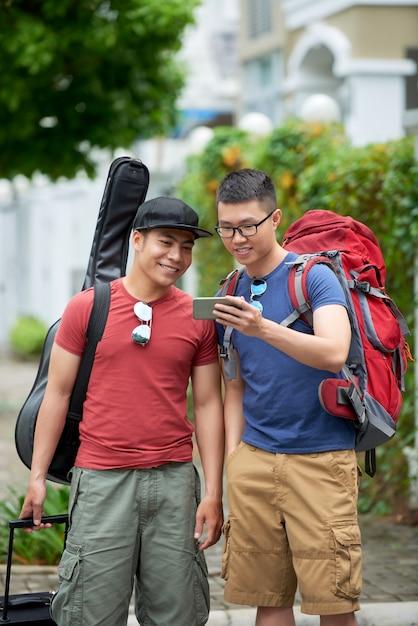 Deux touristes asiatiques mâles regardant un smartphone dans la rue Photo gratuit