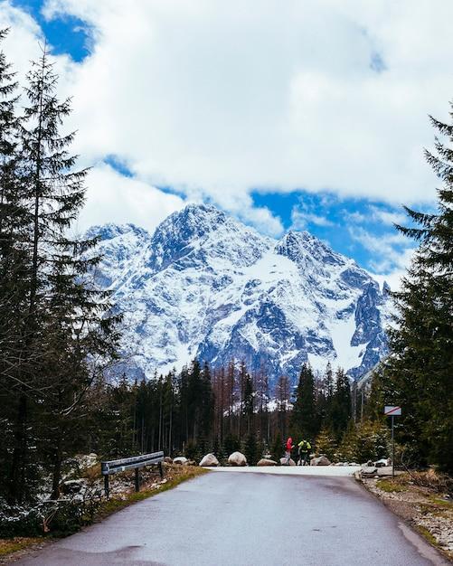 Deux touristes se tenant sur la route près de la montagne enneigée Photo gratuit