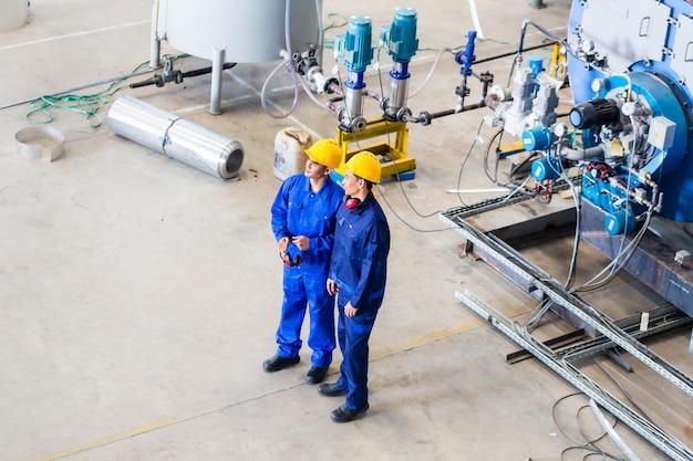 Deux travailleurs dans une usine industrielle discutant Photo Premium