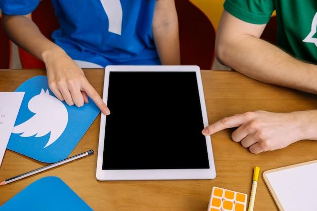 Deux utilisateurs pointant sur une tablette numérique avec écran blanc Photo gratuit