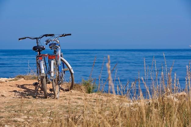 Deux vélos sur la plage sur fond d'une mer bleue par une journée ensoleillée. Photo Premium