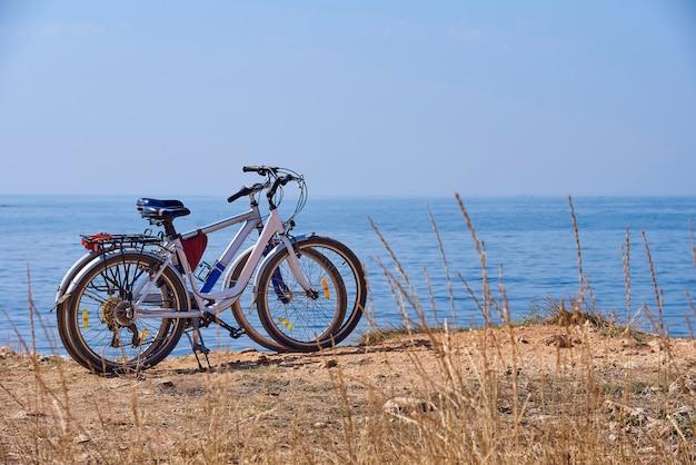 Deux vélos sur la plage par une journée ensoleillée. Photo Premium