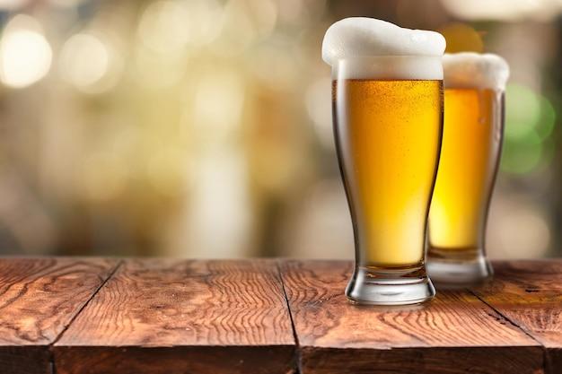 Deux Verre De Bière Avec De La Mousse Sur Une Table En Bois Brun Vide Photo Premium