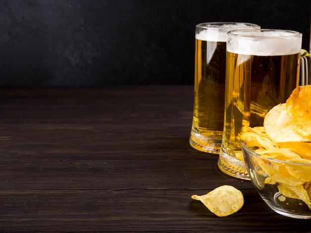Deux Verres De Bière Et Chips Sur Fond Sombre En Bois, Espace Copie Photo Premium