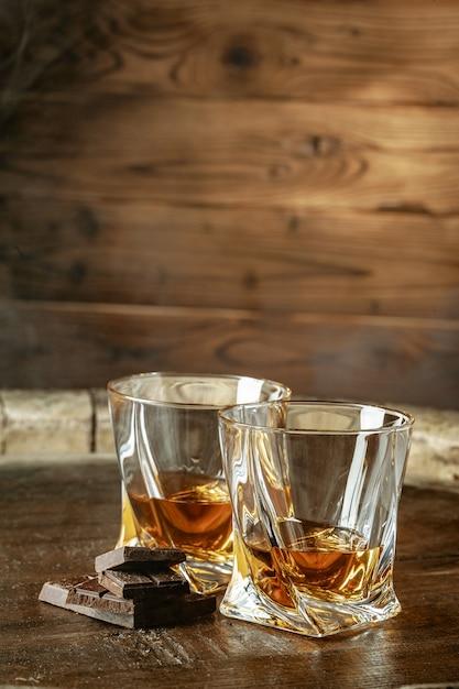 Deux Verres De Bourbon Ou De Scotch, Ou De Cognac Et Des Morceaux De Chocolat Noir Photo Premium