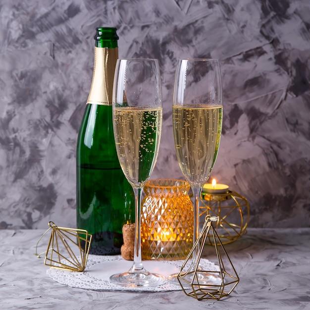 Deux verres de champagne à côté d'une bouteille Photo Premium