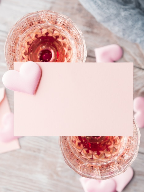 Deux verres de champagne à pied avec carte de note en papier vierge coeurs roses à remplir avec votre texte sur bois texturé. Photo Premium