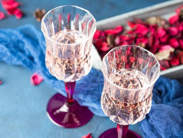 Deux verres de champagne à pied sur fond texturé bleu avec des fleurs séchées roses. Photo Premium