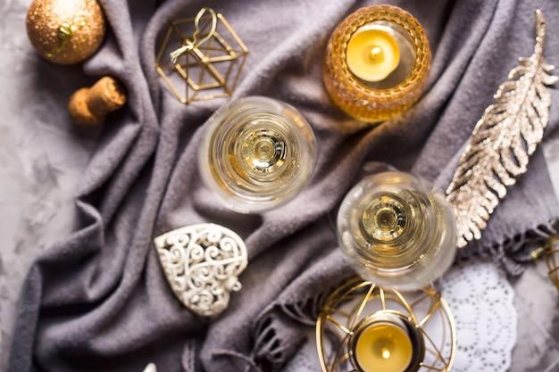 Deux verres de champagne sur un plaid gris parmi or Photo Premium