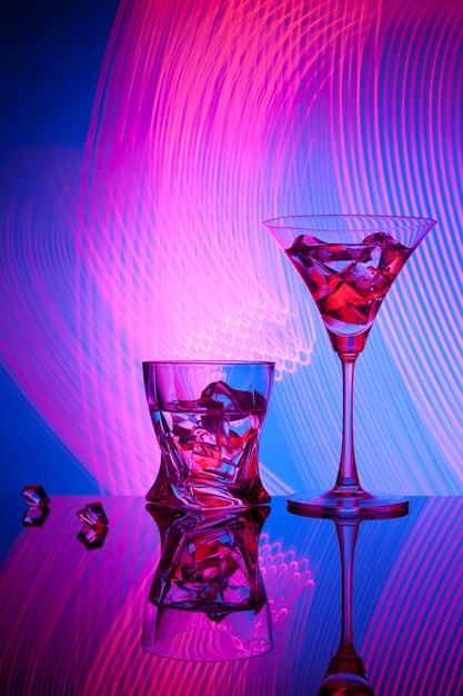 Deux verres de cocktail martini whisky ice, contre le bleu des effets de lumière magnifiques. Photo Premium