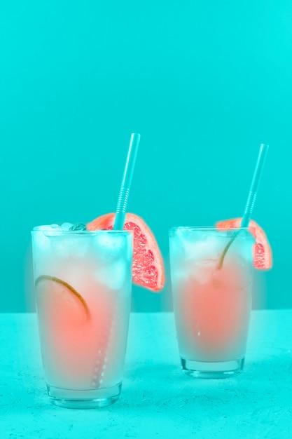 Deux verres de cocktail de pamplemousse rafraîchissement sur fond de menthe Photo gratuit