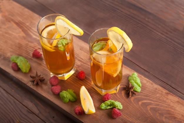Deux Verres Avec Du Kombucha, Des Pailles Et Des Tranches De Citron, Des Framboises Sont Sur Une Table En Bois. Concept De Nourriture Saine. Photo Premium