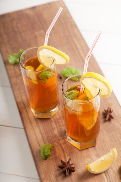Deux Verres Avec Du Kombucha Et Des Tranches De Citron, Des Pailles Et De L'anis étoilé Sur Une Table En Bois. Photo Premium