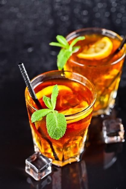 Deux verres avec du thé glacé traditionnel froid avec du citron, des feuilles de menthe et des glaçons. Photo Premium