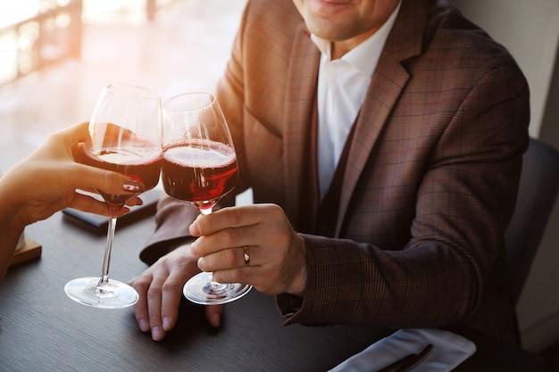 Deux verres de jus de vin rouge. un rendez-vous romantique, un homme et une femme trissent des lunettes. Photo Premium