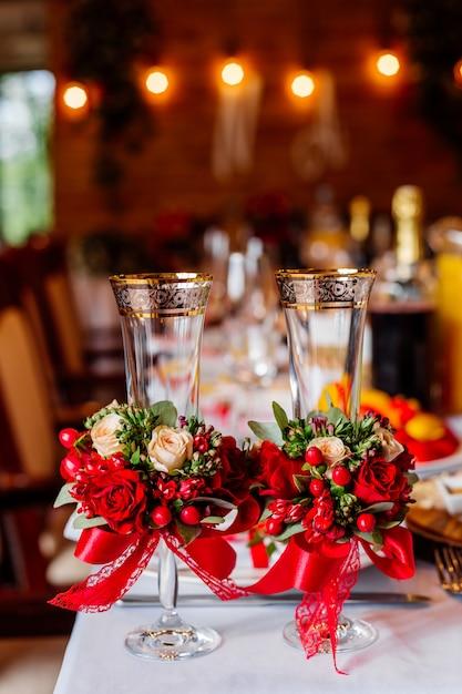 Deux Verres De Mariage Vides, Décorés De Verdure, De Roses Rouges Et De Ruban, Debout Sur La Table De Banquet Photo Premium