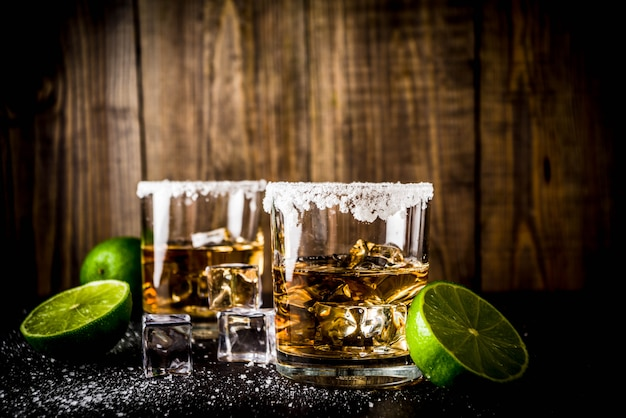 Deux Verres à Tequila Sur Une Table Noire, Avec Des Glaçons, Du Sel Et Du Citron Vert Photo Premium