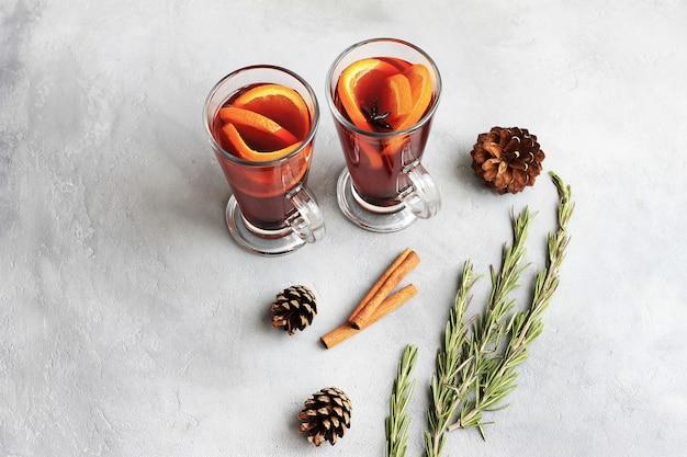 Deux verres de vin chaud rouge ou gluhwein à l'orange, bâtons de cannelle Photo Premium