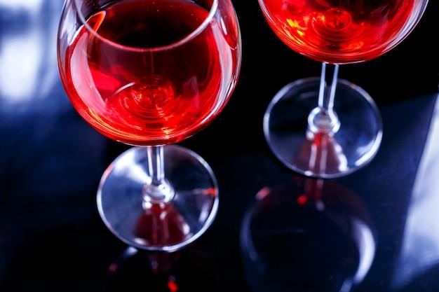 Deux verres de vin rouge au bar, discothèque sur fond noir avec reflet. Photo Premium