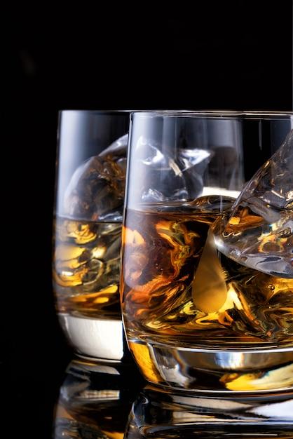 Deux Verres De Whisky Sur La Table Avec Une Bouteille Photo Premium