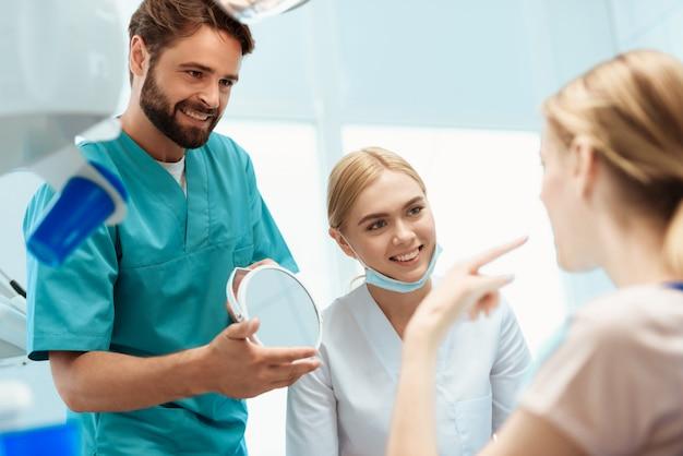 Devant elle, un médecin tient un miroir dans ses mains. Photo Premium
