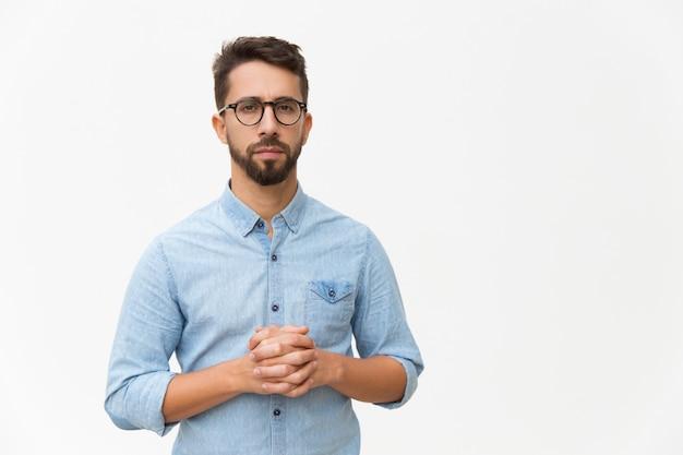 Devant Un Homme Confiant Sérieux Avec Les Mains Jointes Photo gratuit