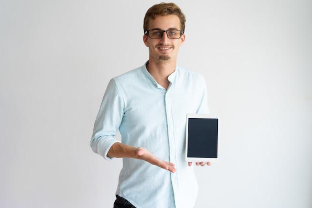 Développeur gai application mobile dans des verres montrant l'écran de la tablette et en regardant la caméra. Photo gratuit