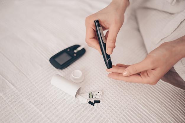 Diabète Vérifiant La Glycémie. Femme à L'aide De Lancette Et Glucomètre Numérique à La Maison. Médecine, Diabète De Régime, Concept De Soins De Santé - Mains Féminines Avec Glucomètre Vérifiant Le Niveau De Glucose Corporel Photo Premium