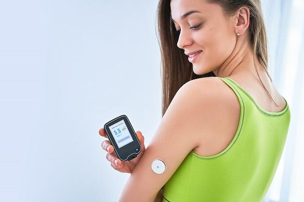 Les Diabétiques Contrôlent Et Vérifient Le Niveau De Glucose Avec Un Capteur à Distance. Surveillance Continue Des Niveaux De Glucose Sans Sang. Technologie Médicale Dans Le Traitement Du Diabète Sucré Photo Premium
