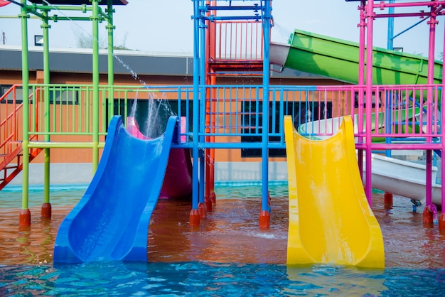 Diapositives en plastique coloré dans le parc aquatique à la lumière du soleil Photo gratuit